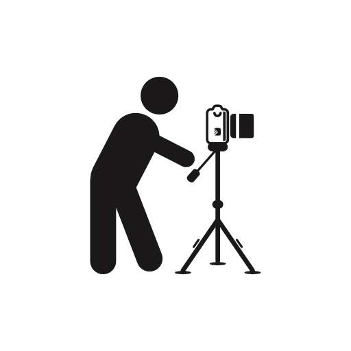 Photographer Standing Behind Photo Camera On A Tripod From Side