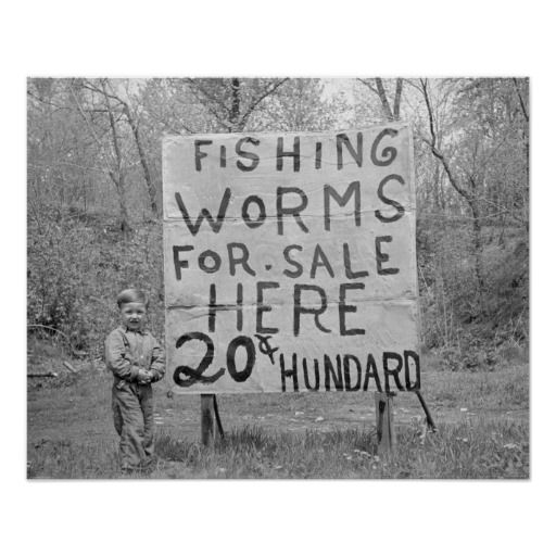 A Little Boy Stands Next To A Hand Painted Sign Advertising