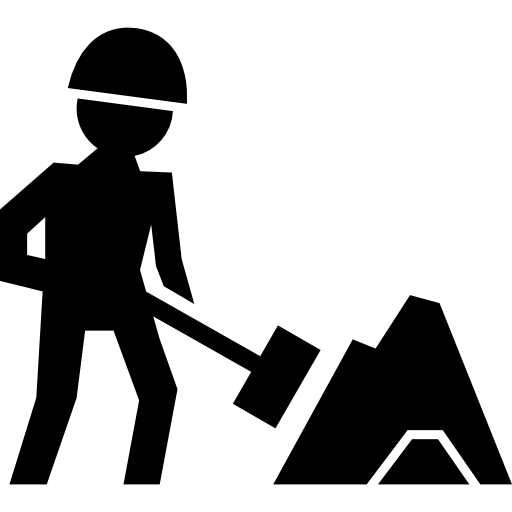 Worker Of Construction Working With A Shovel Beside Material Pile