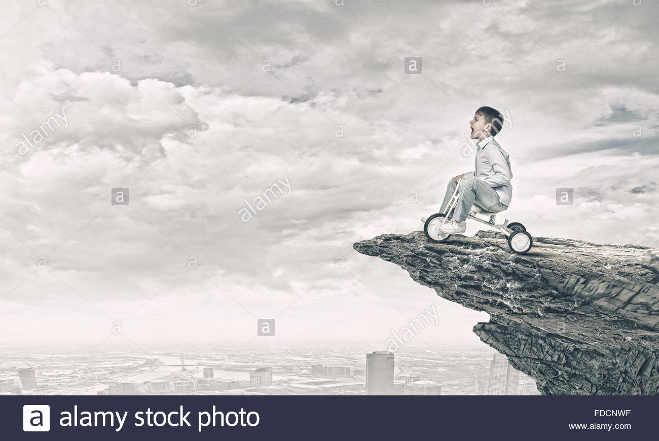 1300x870 Little Joyful Cute Boy Riding Tricycle On Cliff Edge Stock Photo