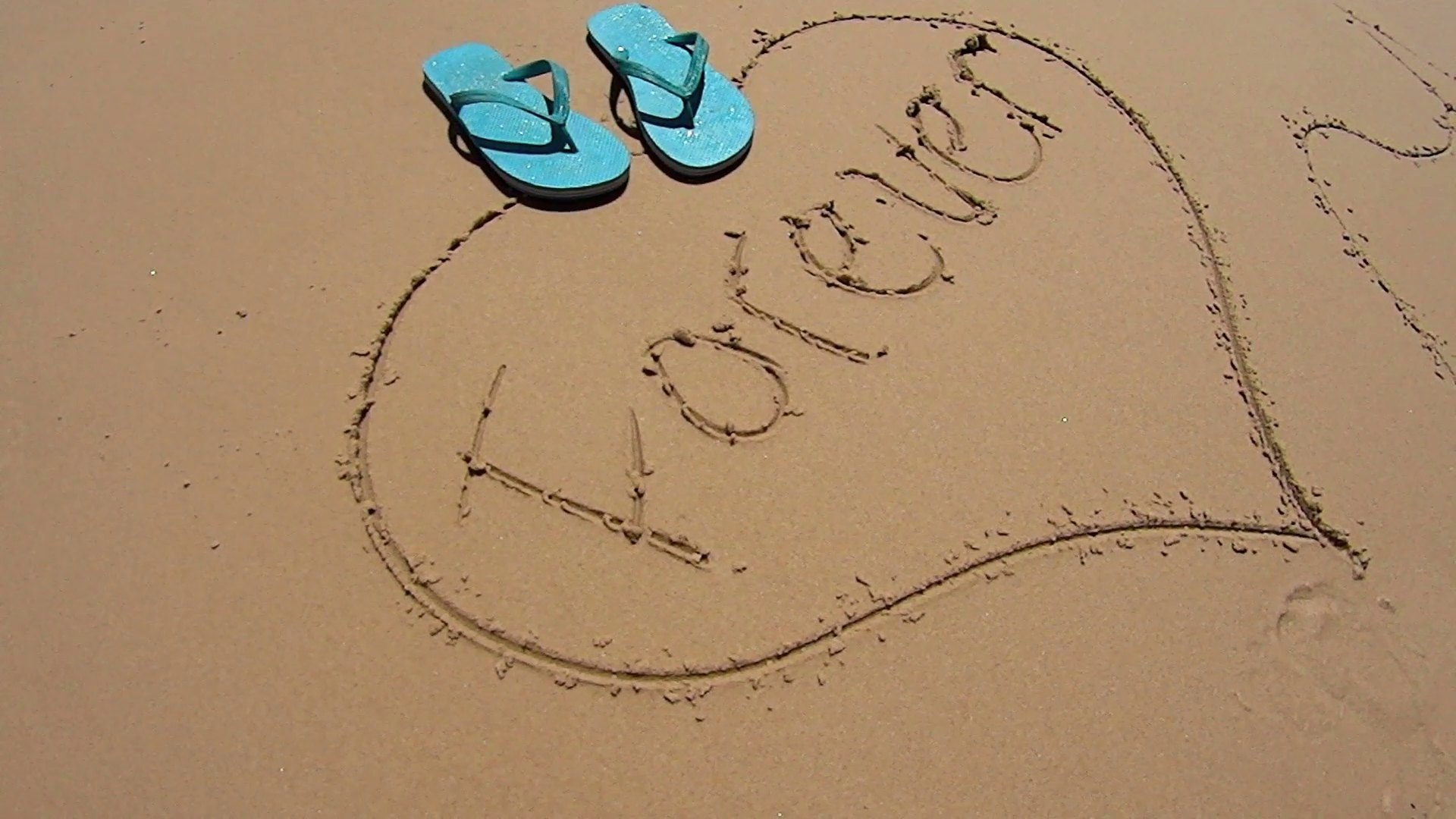 1920x1080 Pair Of Flip Flops Dropped On Love Heart Drawn In The Sand On