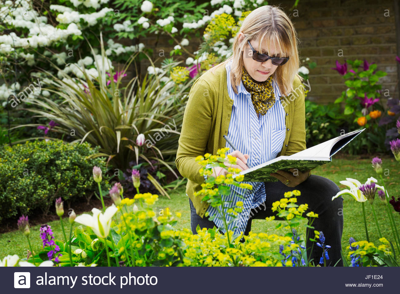 1300x956 Woman Wearing Sunglasses Standing In A Garden By A Flowerbed