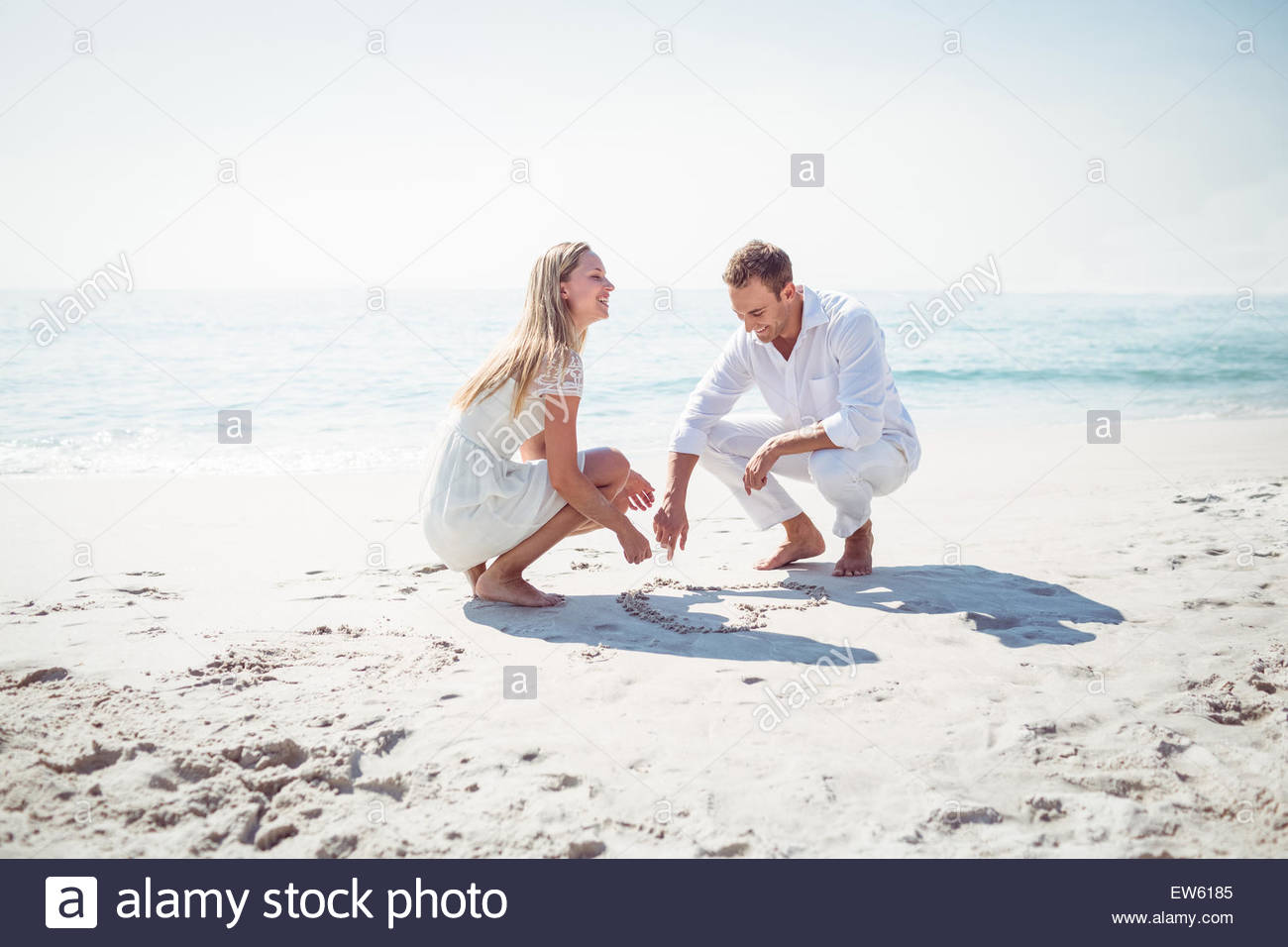 1300x956 Happy Couple Drawing Heart Shape In The Sand Stock Photo, Royalty