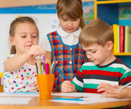 450x374 Cute Little Children Drawing With Teacher At Preschool Class Stock