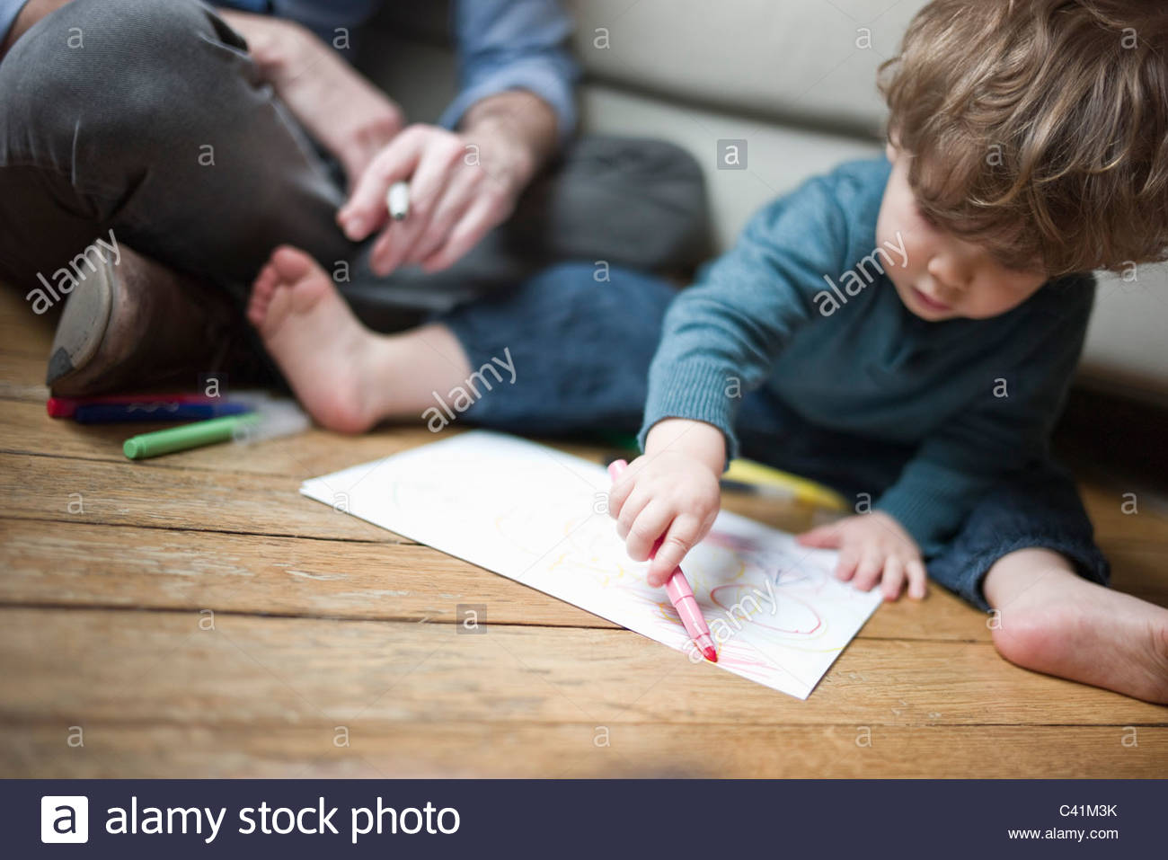 1300x957 Toddler Boy Sitting On Floor With Parent, Drawing On Paper Stock