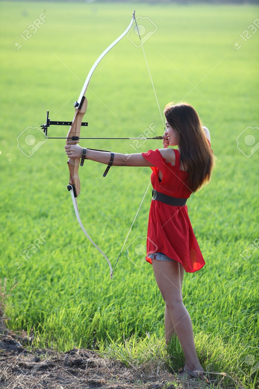 866x1300 Girl Drawing Recurve Bow In Paddy Field Stock Photo, Picture