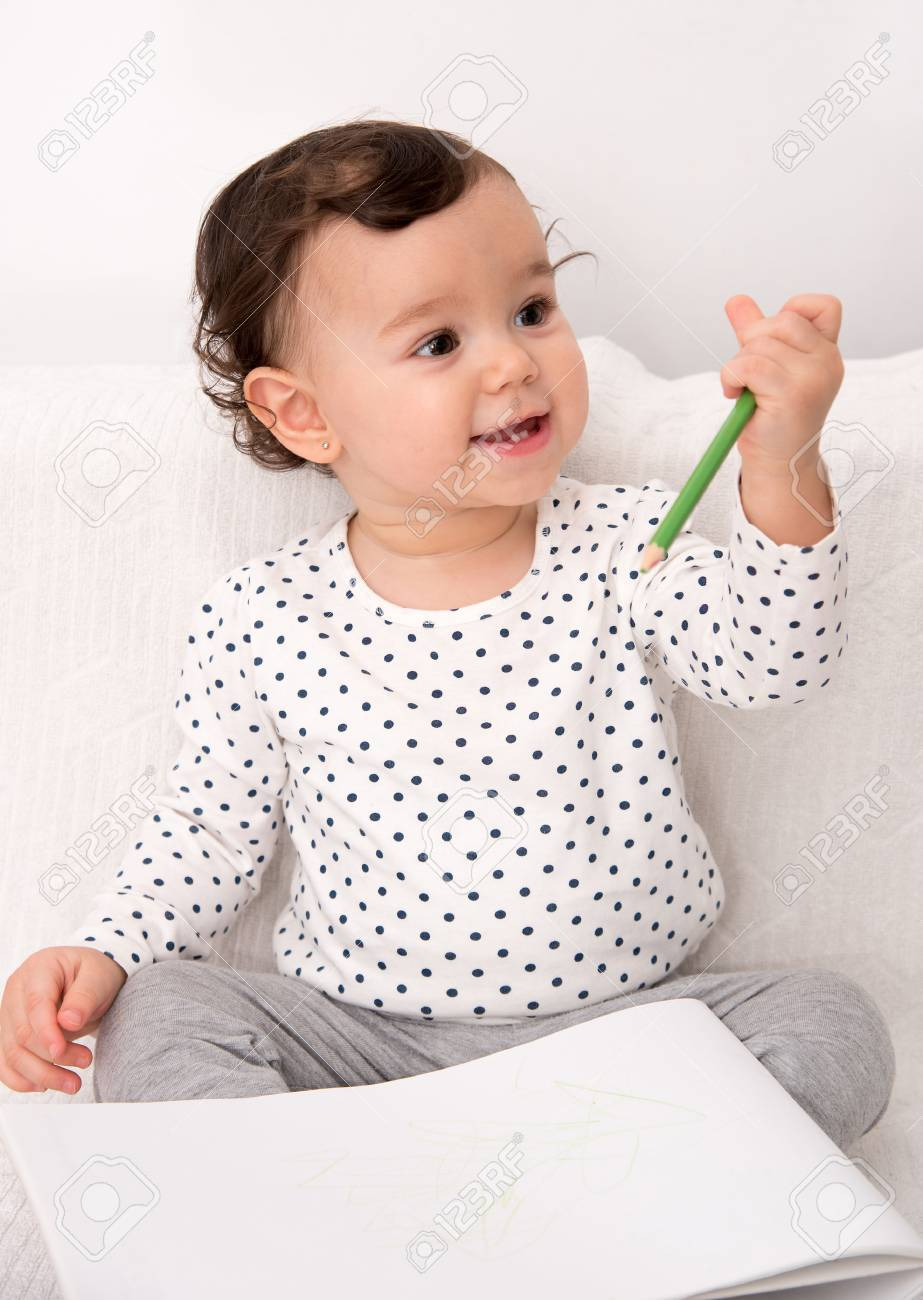 923x1300 Smiling Baby Girl Sitting On The Bed And Drawing With A Colored