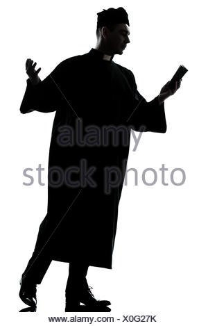 300x469 One Caucasian Man Priest Reading Bible Silhouette In Studio