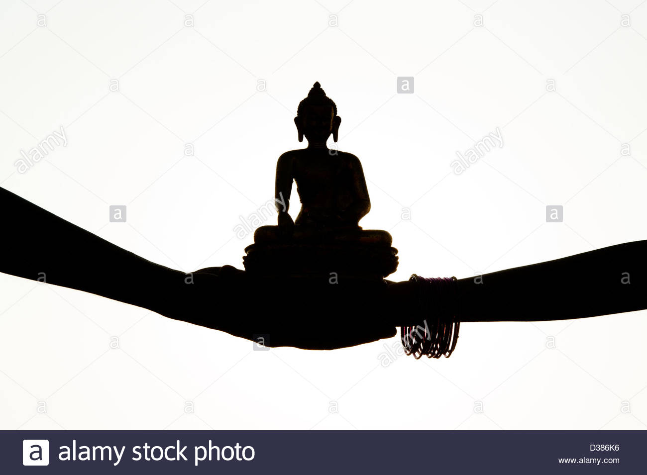 1300x955 Indian Hands Holding A Buddha Statue. Silhouette Stock Photo