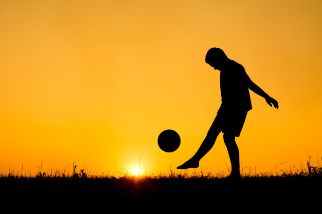 626x417 Silhouette Of Boy Playing Football During Sky Sunset Background