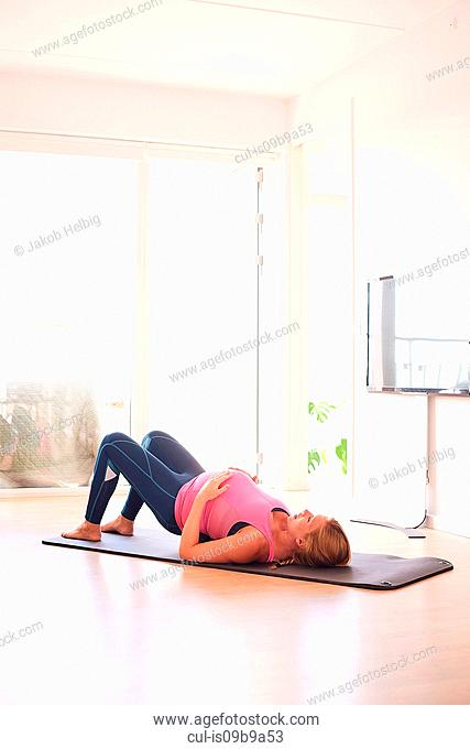 427x680 Woman Exercising Lying On Back Fitness Yoga Stretching In Shadow